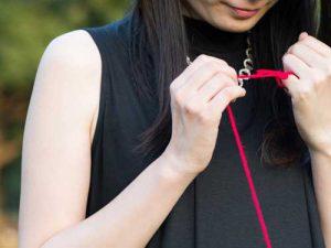 小指に結んでいる赤い糸を見つめる女性