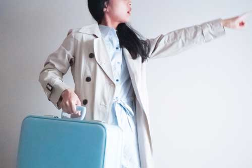 旅行カバン片手に指差す女性