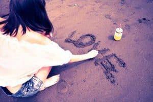 砂浜にLOVEと書く女性