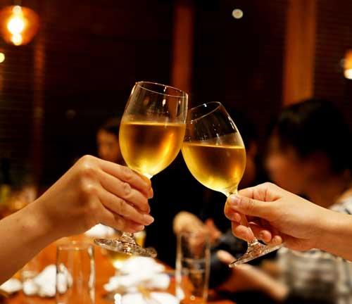 白ワインで乾杯する女性の手