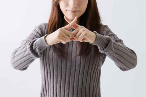 指で×をする女性