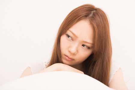 枕を抱え考える女性